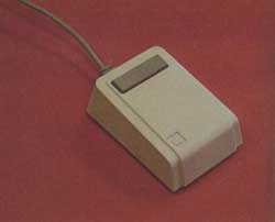 "Photo 3: The ""mouse"" pointing device is about the size of a package of cigarettes and has one button on top."